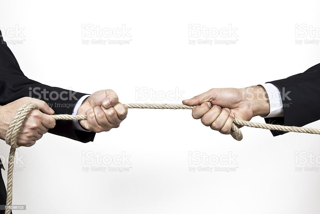 Two business people pulling rope in tug of war on white stock photo