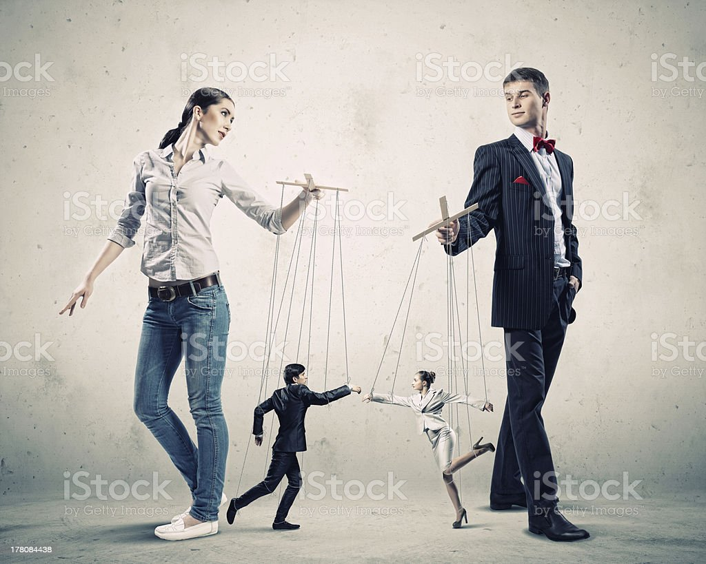 Two business people pulling strings on two other people stock photo