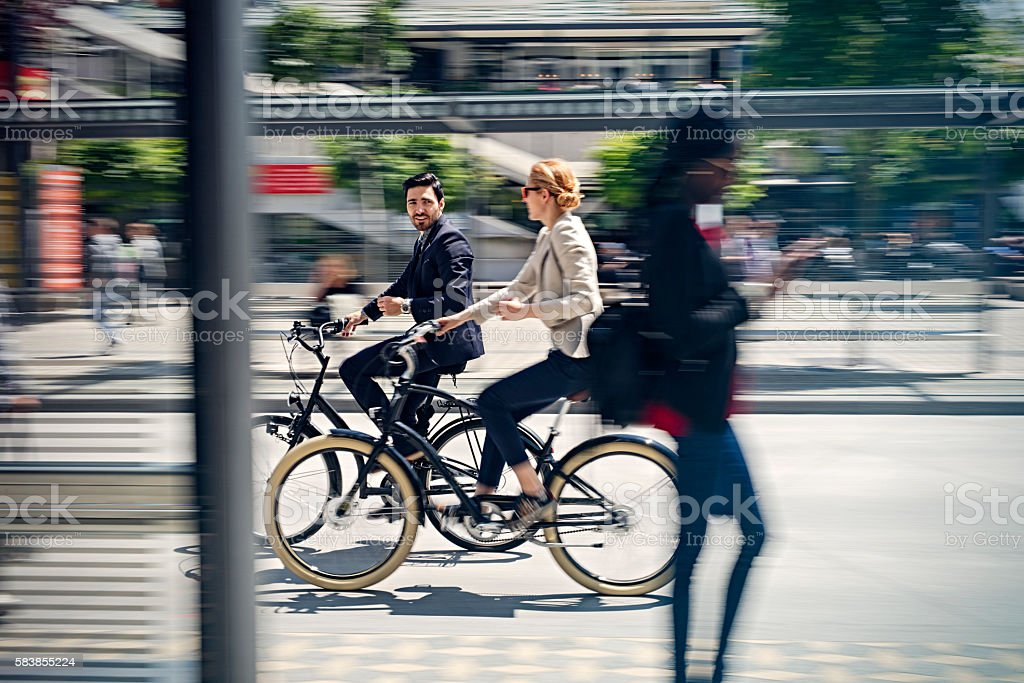 two business people riding bicycle stock photo