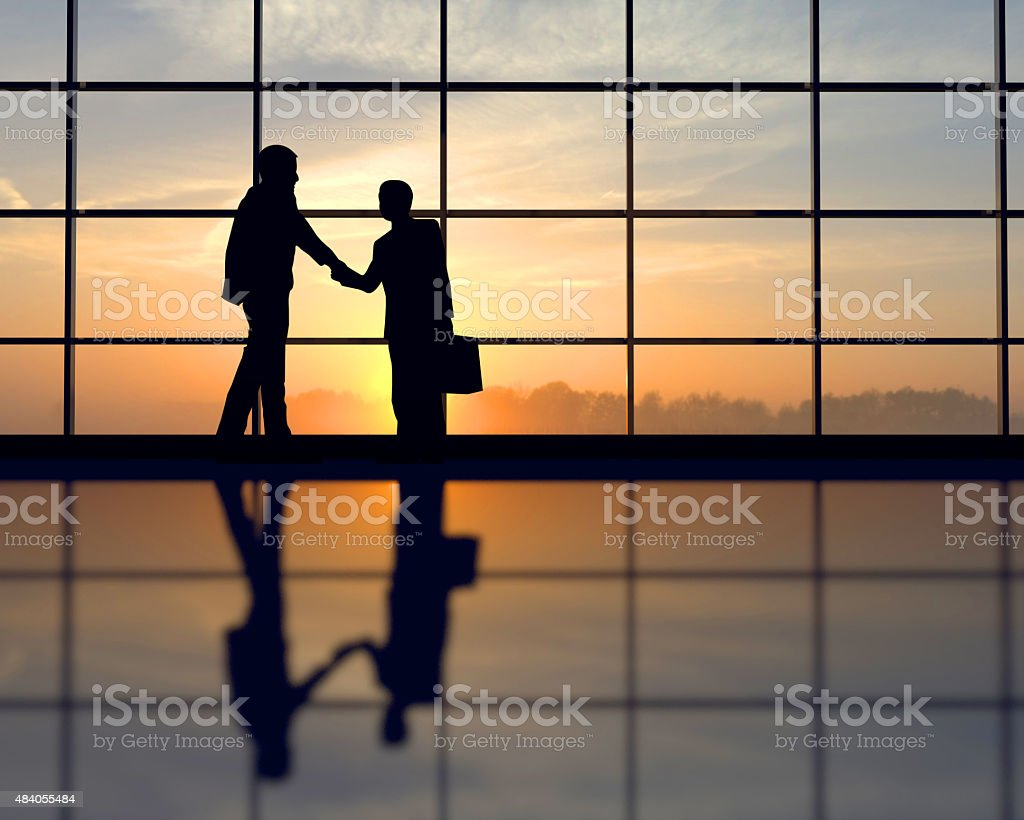 Two business people shake hands against sunset stock photo