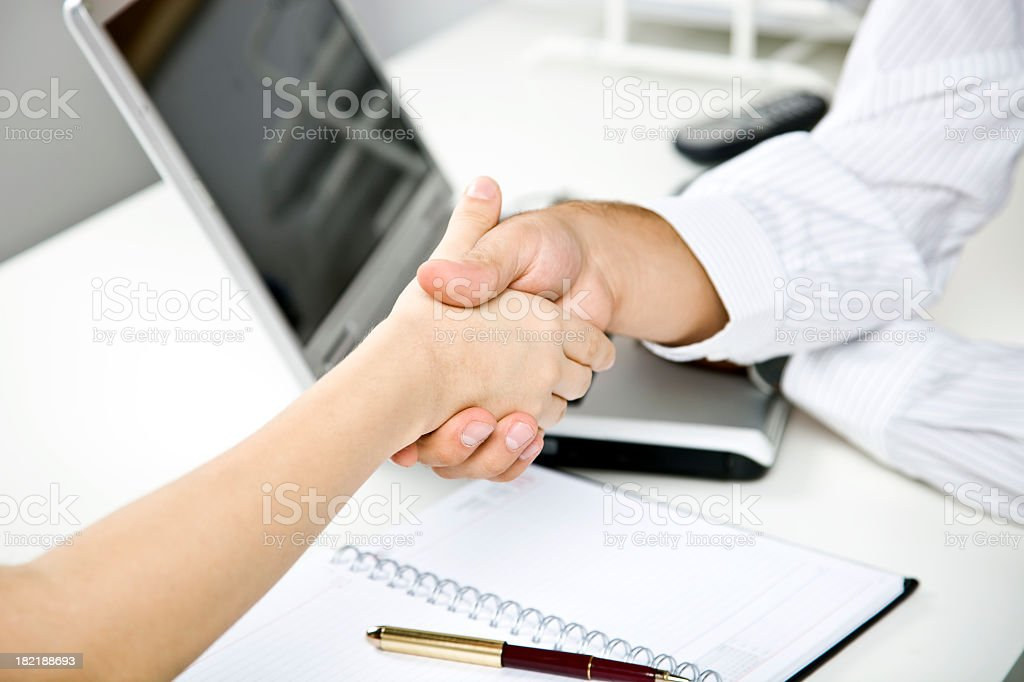 Two business people shake hands over laptop stock photo