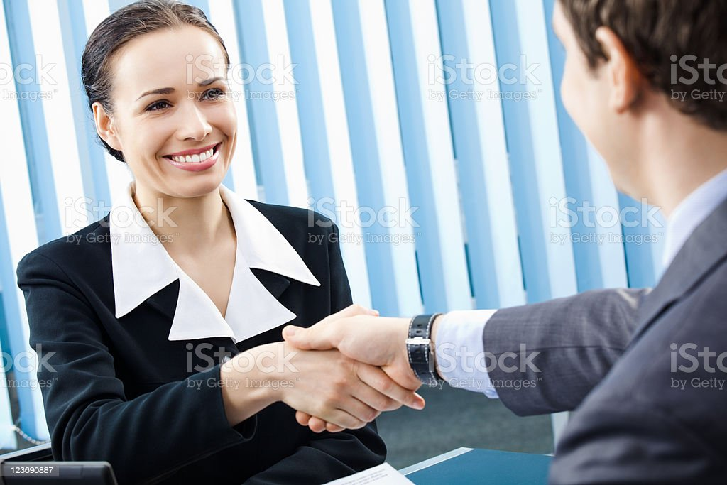 Two business people shaking hands at the office royalty-free stock photo