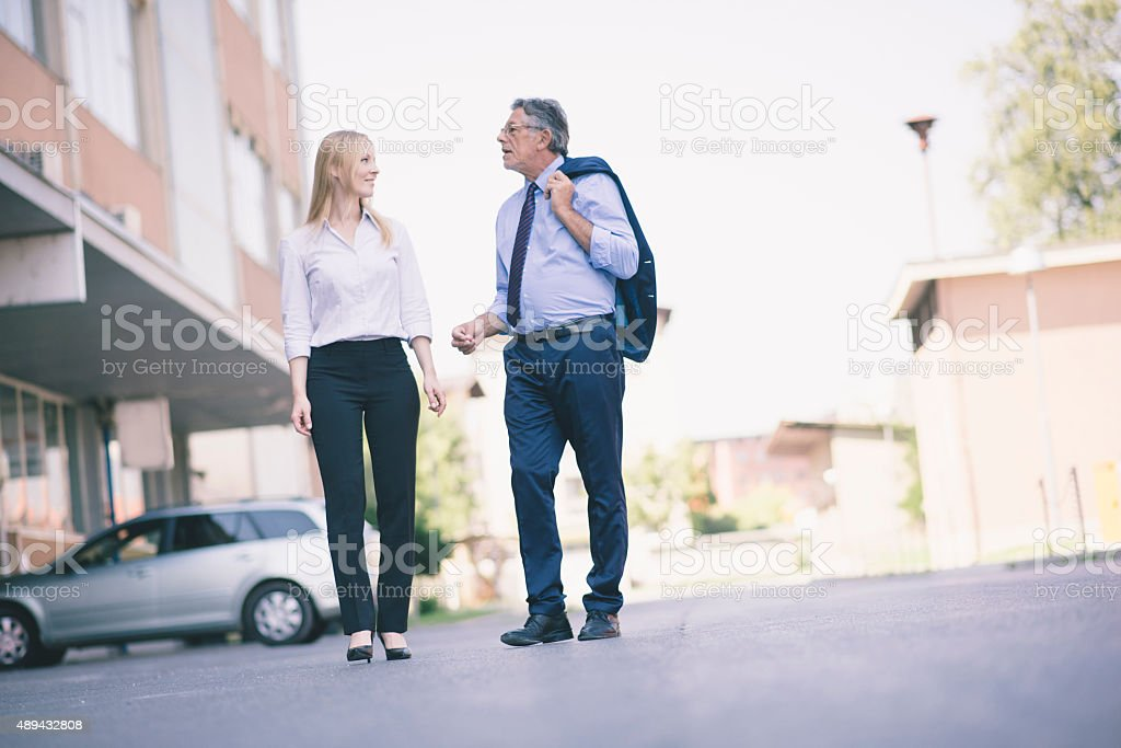 Two business people taking a walk and talking stock photo