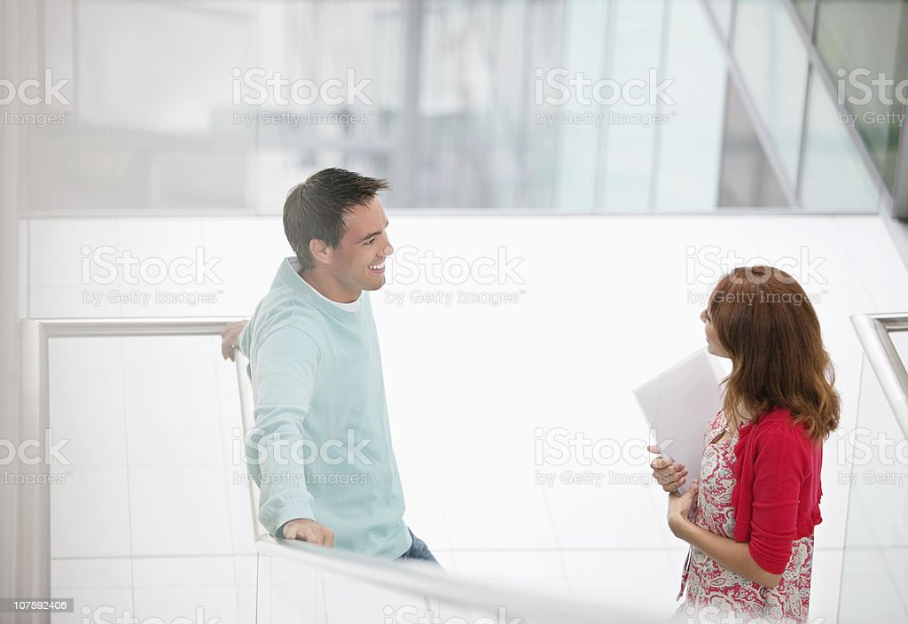 Two business people talking near staircase at office lobby stock photo