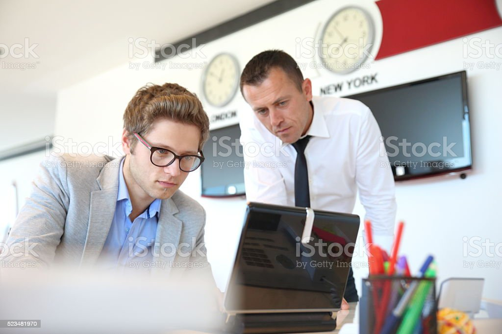 Two business people using a laptop stock photo