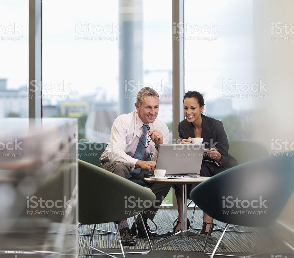 Two business people using laptop at office cafeteria royalty-free stock photo