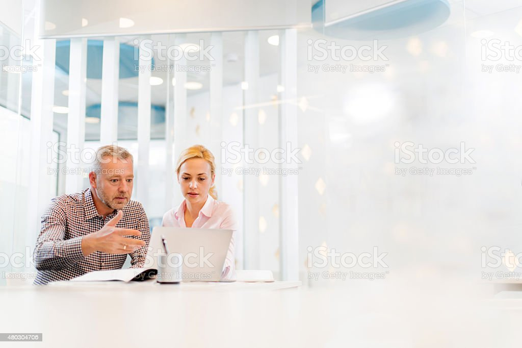 Two business people working together on laptop. stock photo