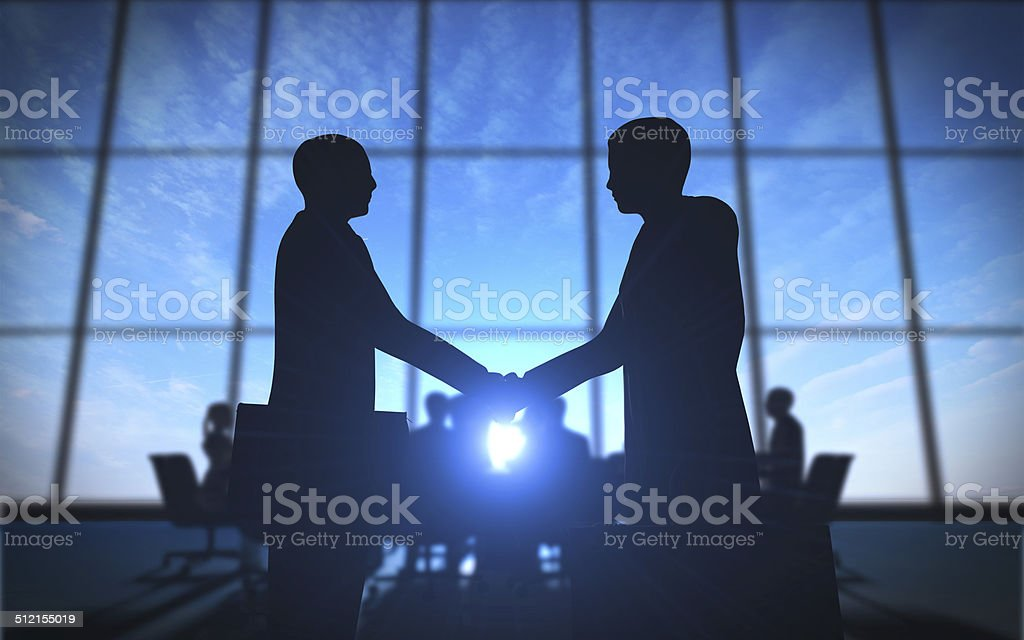 Two business shake hand in office silhouettes stock photo