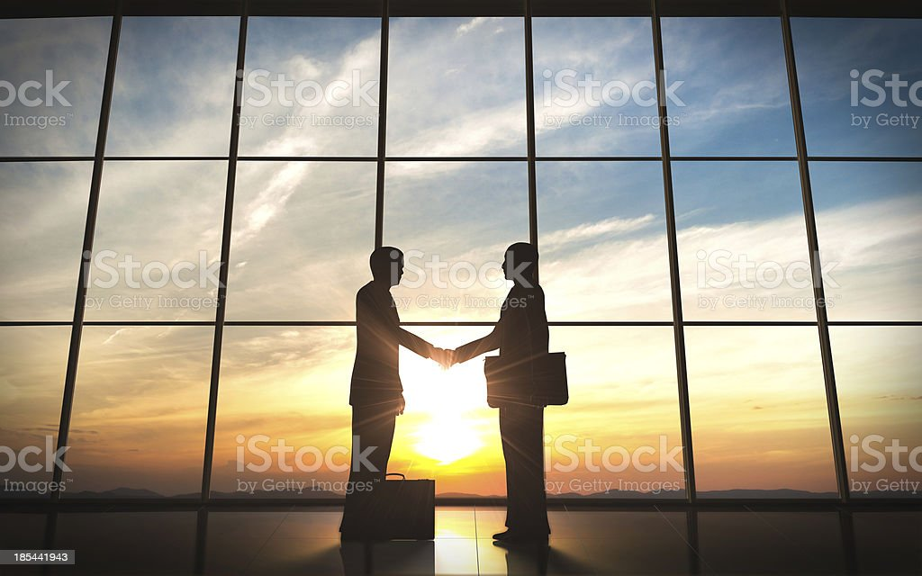 Two business shake hand silhouettes stock photo