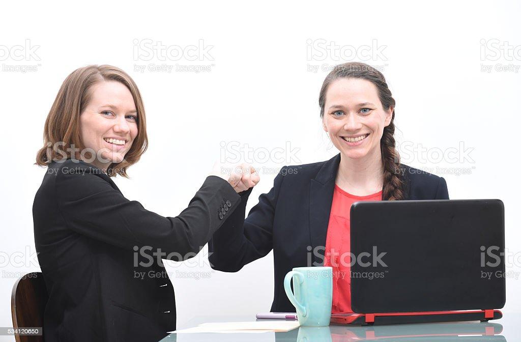 Two business women doing fist bump stock photo