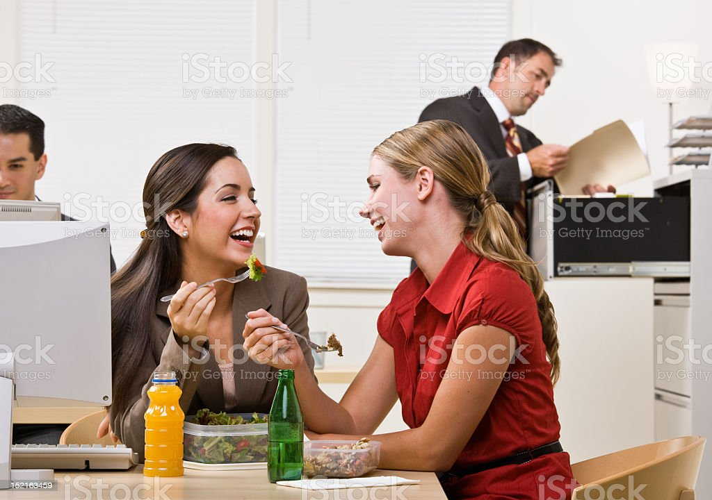 Two business women enjoying a salad for lunch royalty-free stock photo