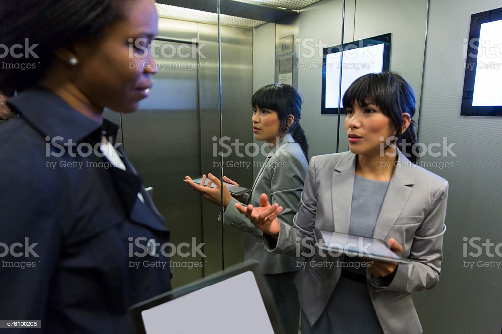 Two business women in elevator discussing,using digital tablets stock photo