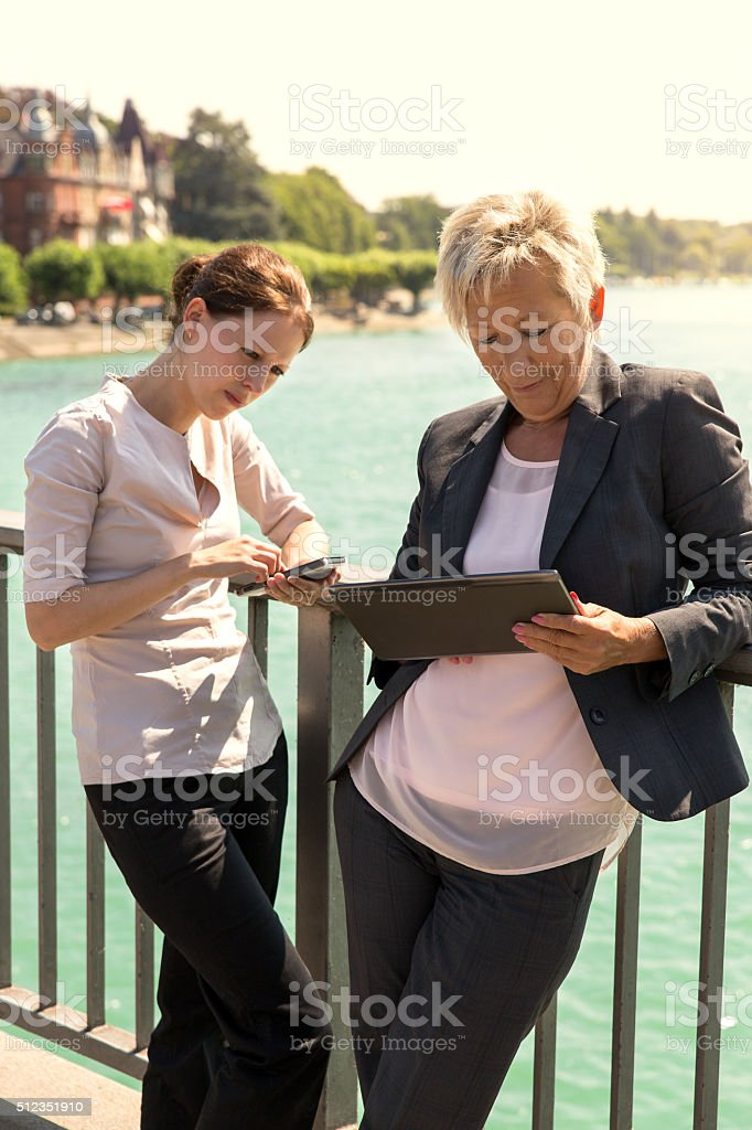 two business women with tablet and smartphone working outside th stock photo