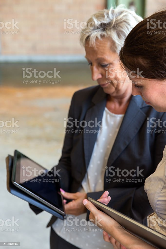 two business women with tablets in a warehouse stock photo