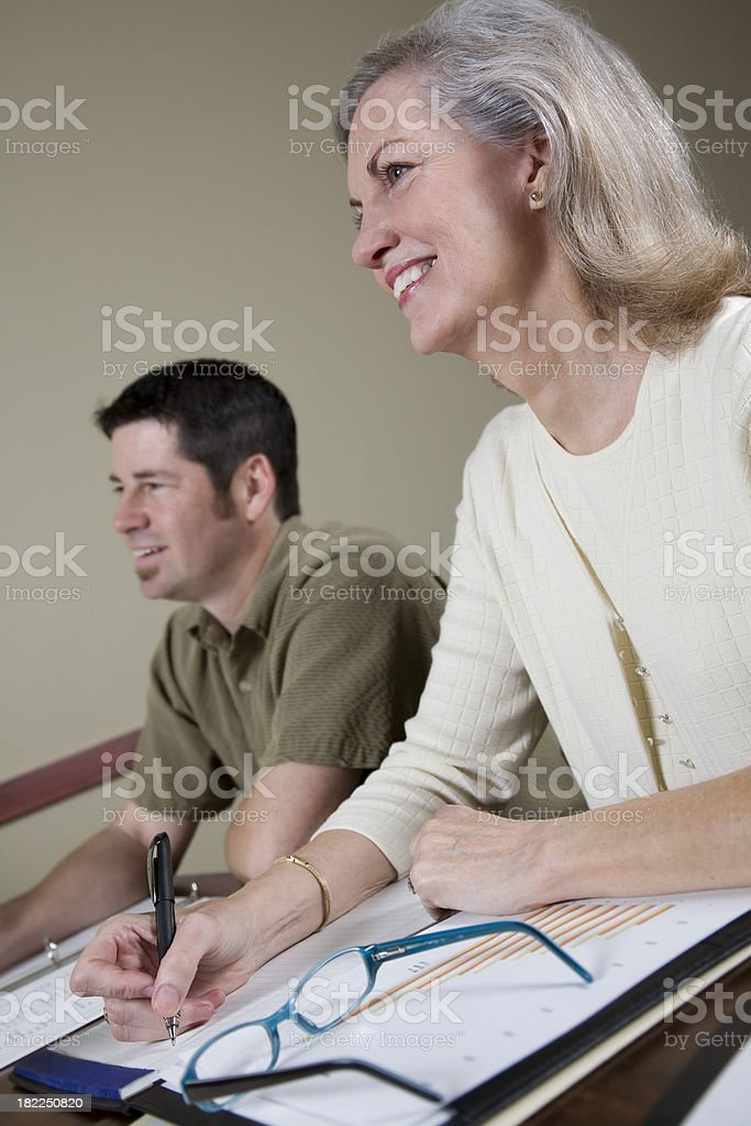 Two Business Workers Listening to Presentation royalty-free stock photo