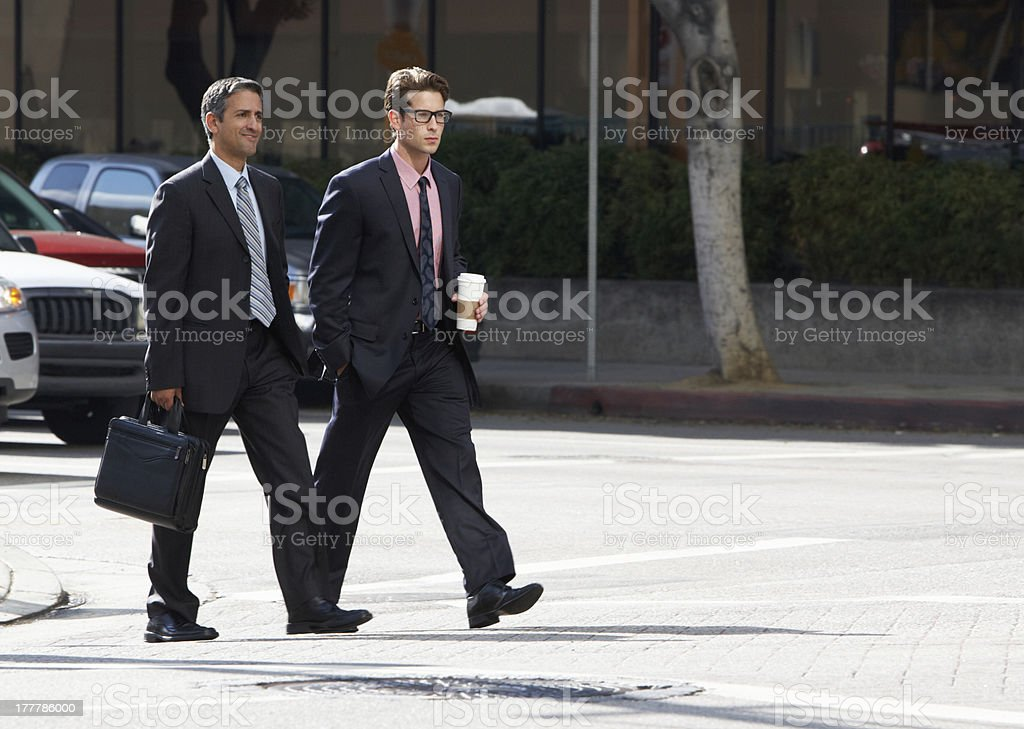 Two Businessman Chatting Whilst Crossing Street royalty-free stock photo