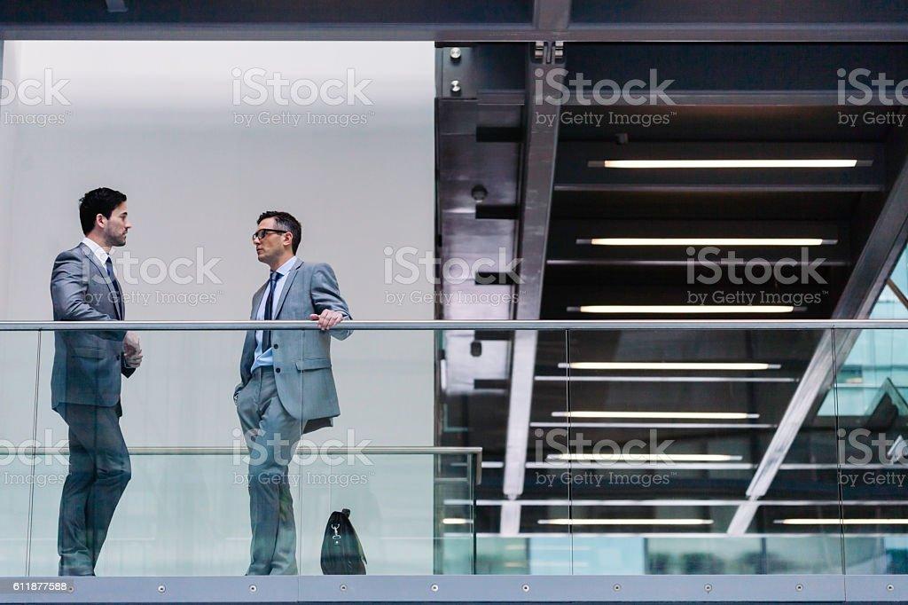 Two businessman meet in the corridor stock photo