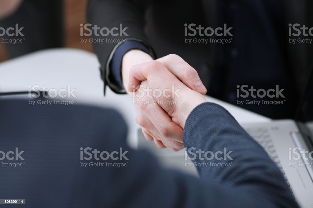 Two businessman shake hands as hello in office closeup stock photo