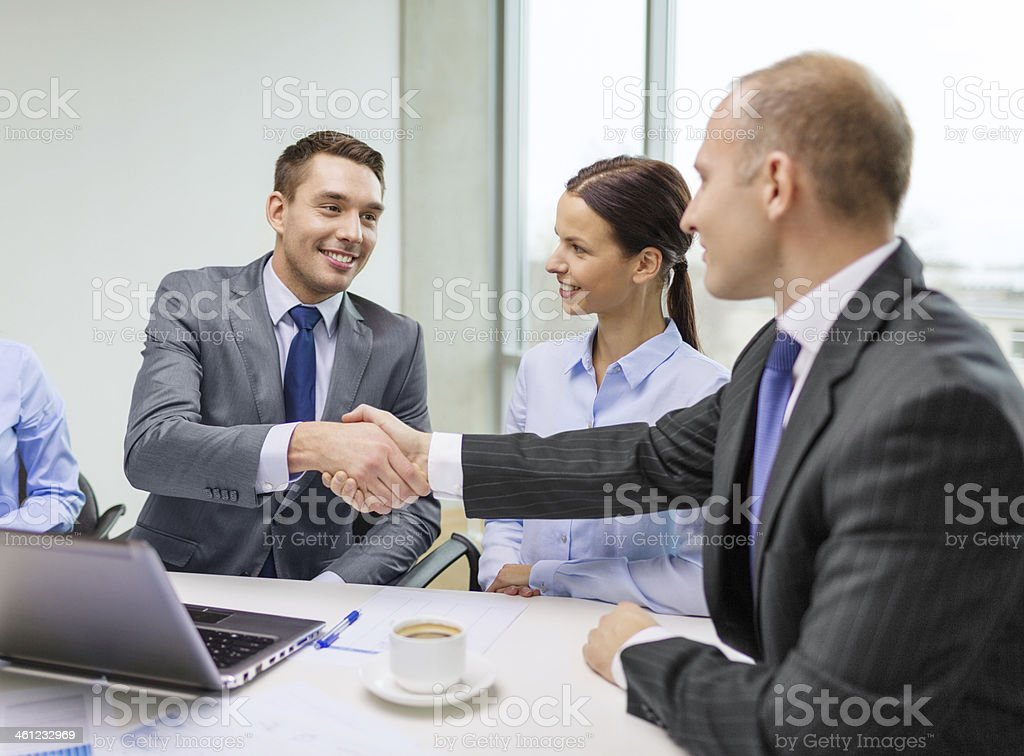 two businessman shaking hands in office stock photo
