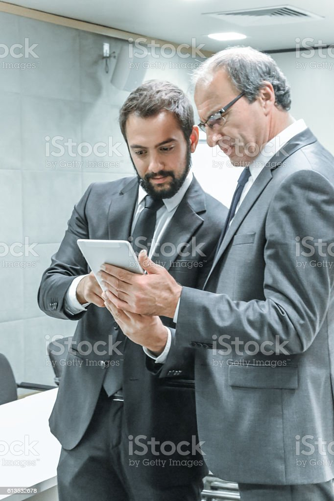 Two businessman working on mobile device stock photo