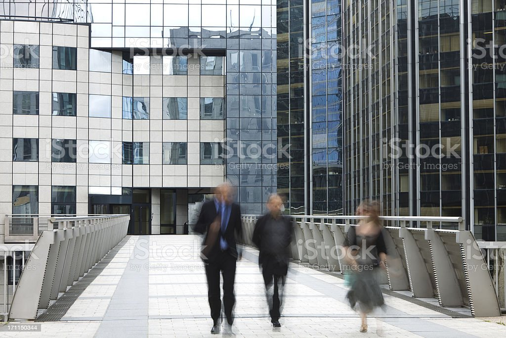 Two Businessmen and Businesswoman Walking in Front of Office Building royalty-free stock photo