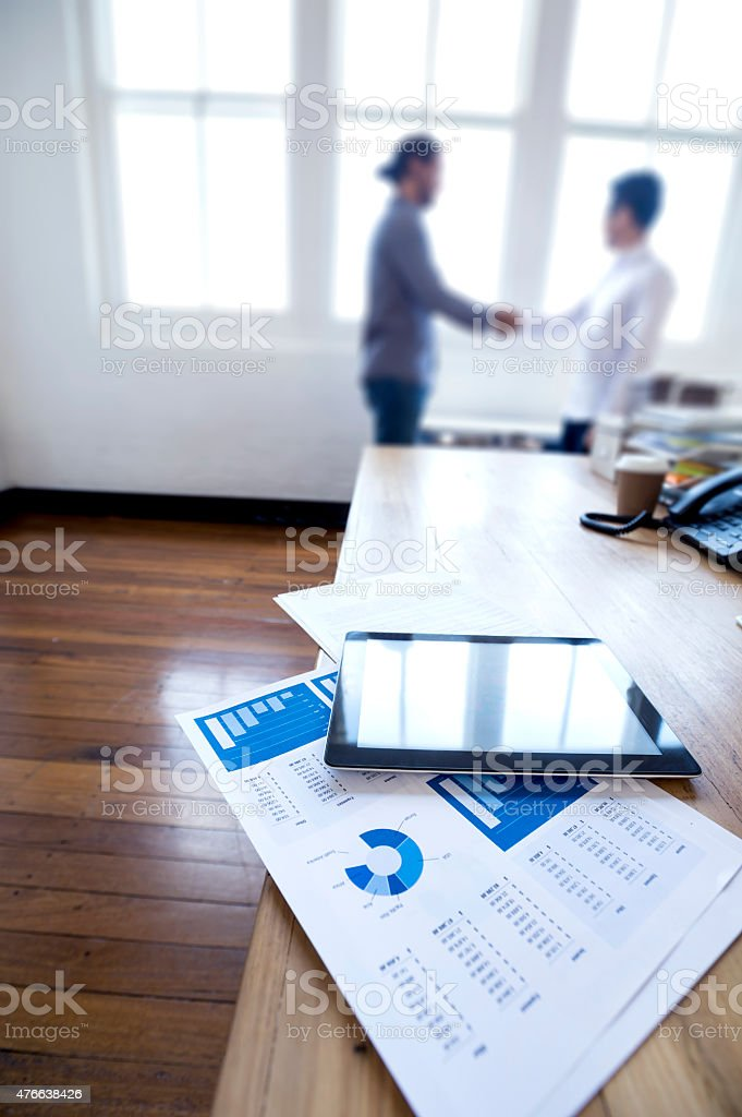 Two businessmen are shaking hands in the background. stock photo