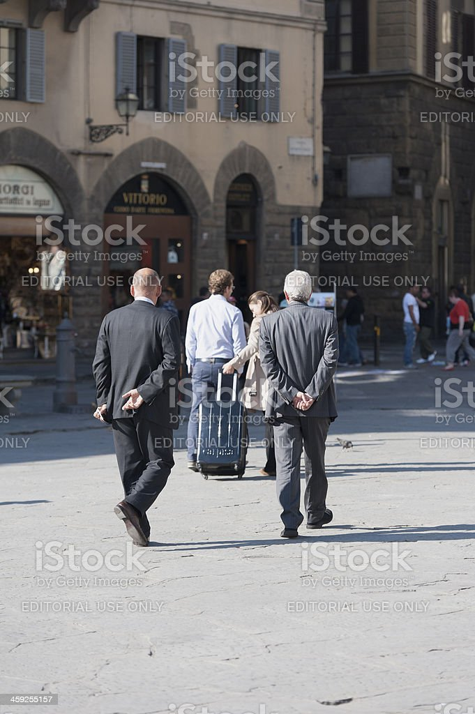 two businessmen are walking and talking on piazza della repubblica royalty-free stock photo