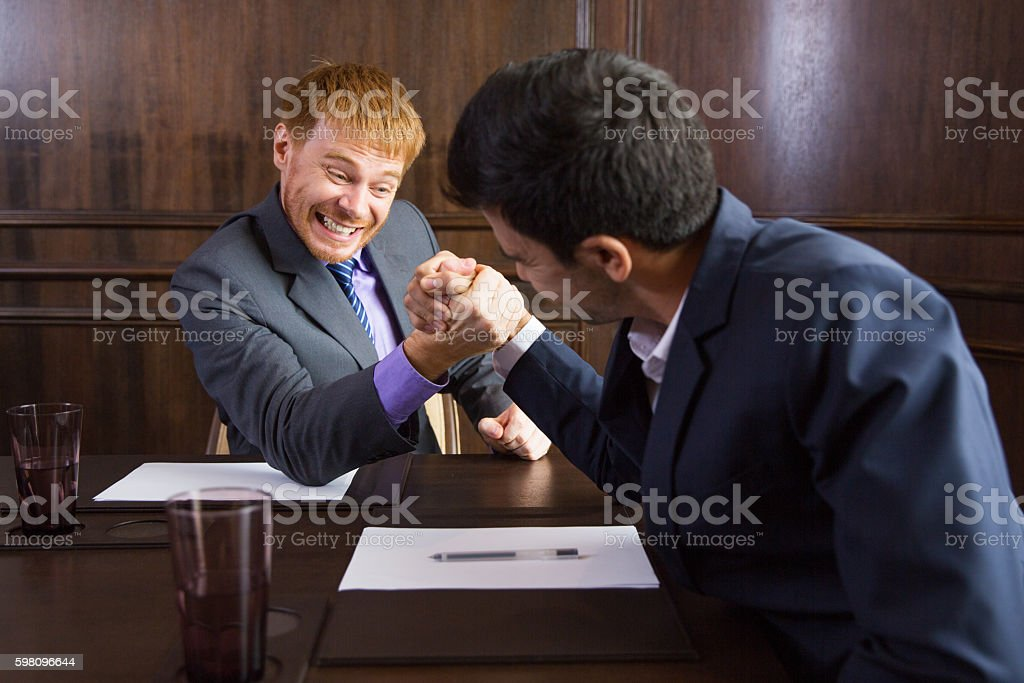 Two Businessmen Arm Wrestling in Modern Office stock photo