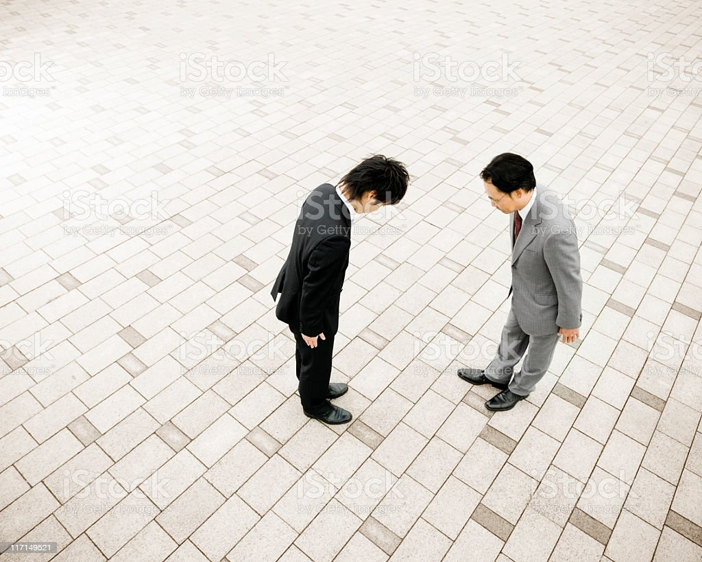 Two Businessmen Bowing in Respect royalty-free stock photo