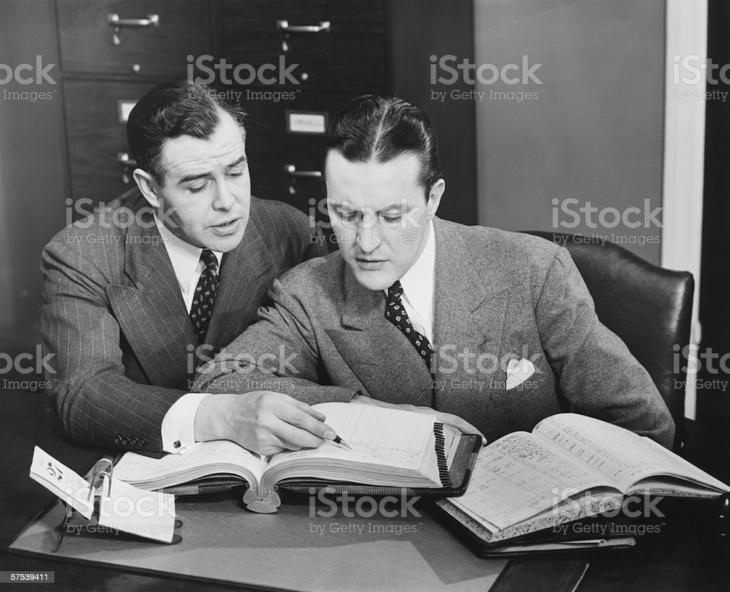 Two businessmen checking trading books, (B&W) royalty-free stock photo