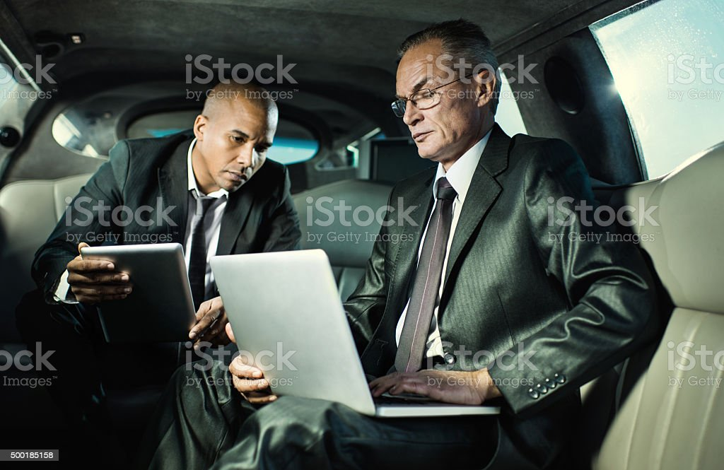 Two businessmen driving to work and using wireless technology. stock photo