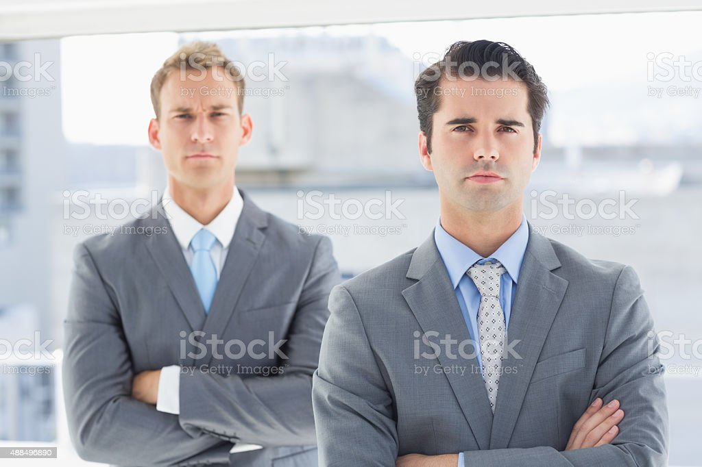 Two businessmen frowning at camera stock photo