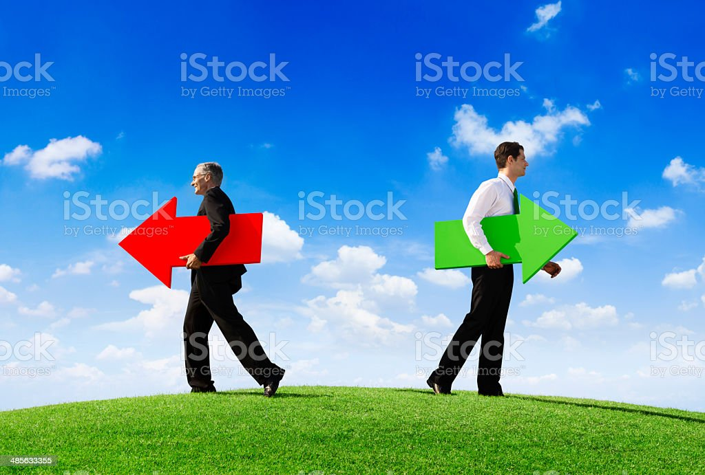 Two Businessmen Holding Contrasting Arrows Making Seperate Ways stock photo