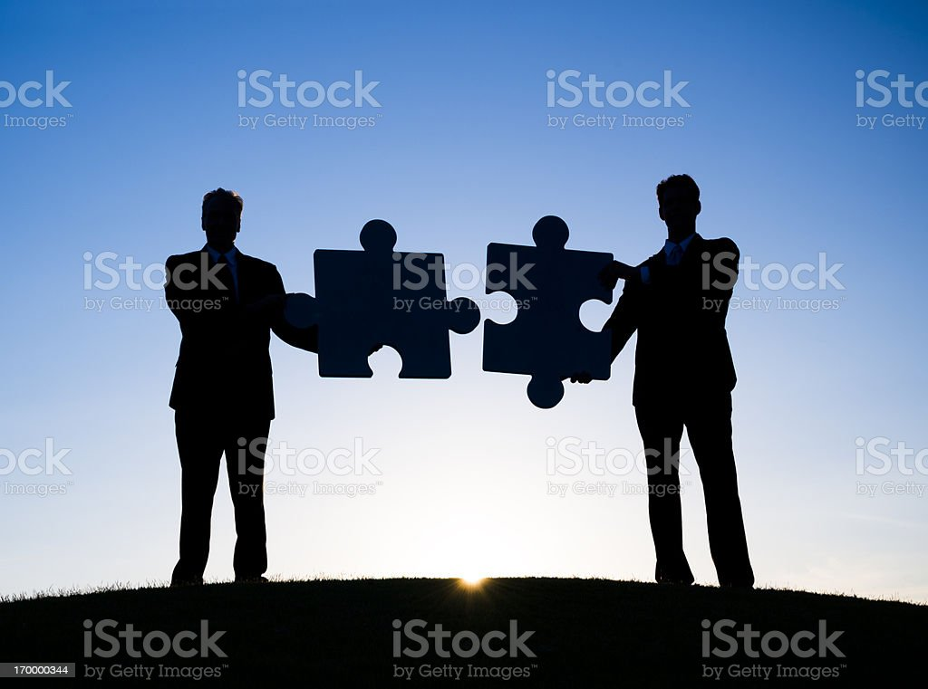 Two Businessmen holding the jigsaw puzzle stock photo