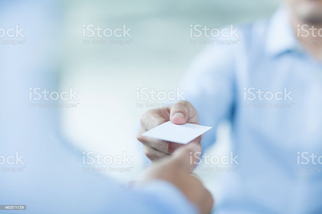 Two businessmen in blue shirts exchanging business cards stock photo