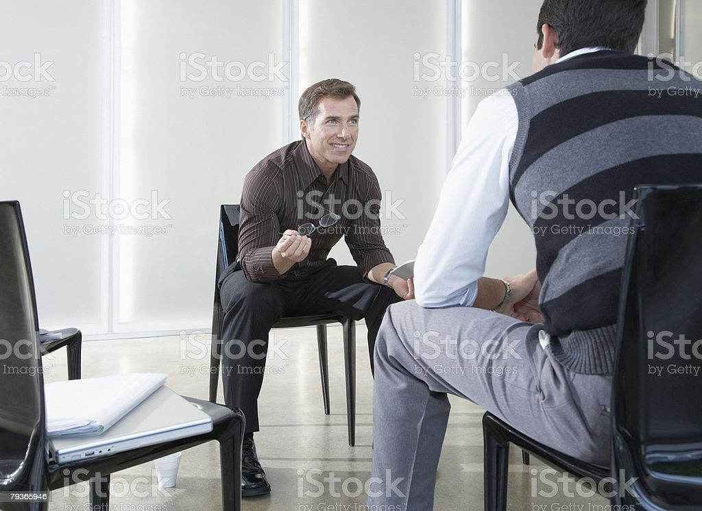 Two businessmen in boardroom talking royalty-free stock photo