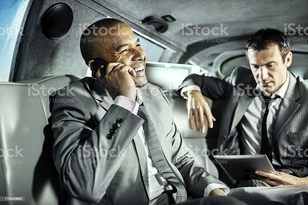 Two businessmen in gray suits in limousine royalty-free stock photo