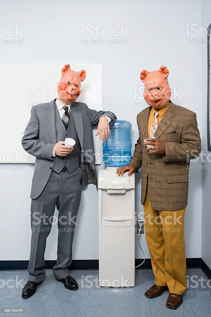 Two businessmen in pig masks stock photo