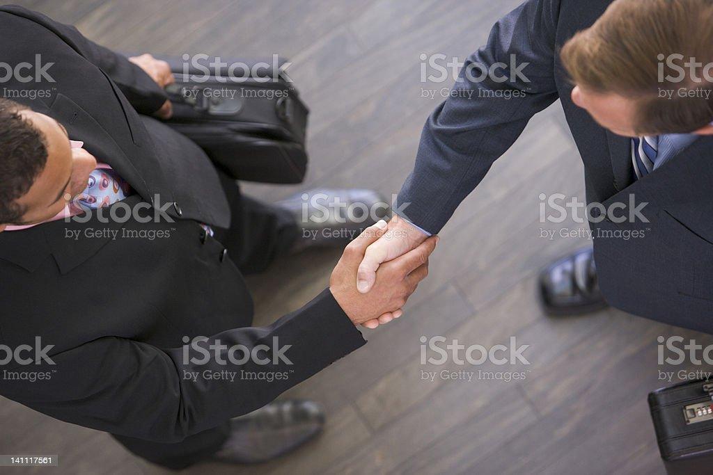 Two businessmen indoors shaking hands stock photo