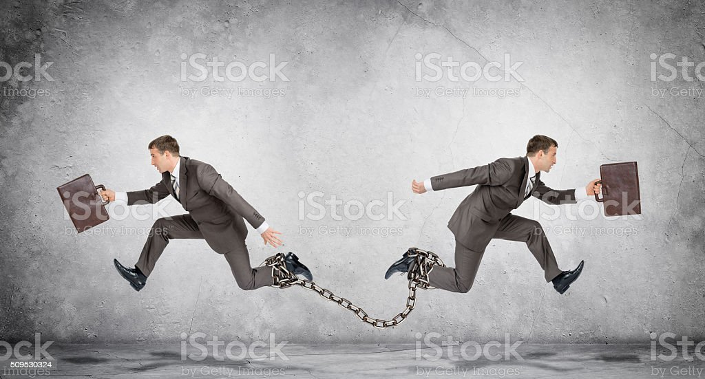 Two businessmen linked chain running stock photo