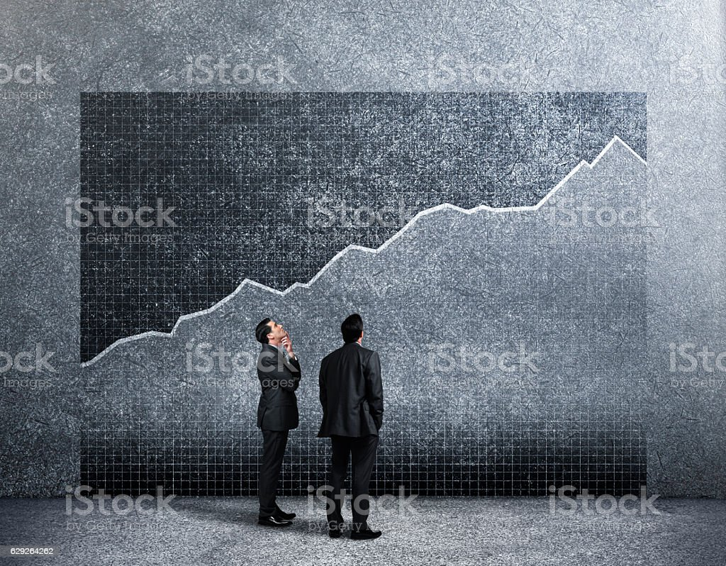 Two Businessmen Looking Up At Growth Chart On Wall stock photo