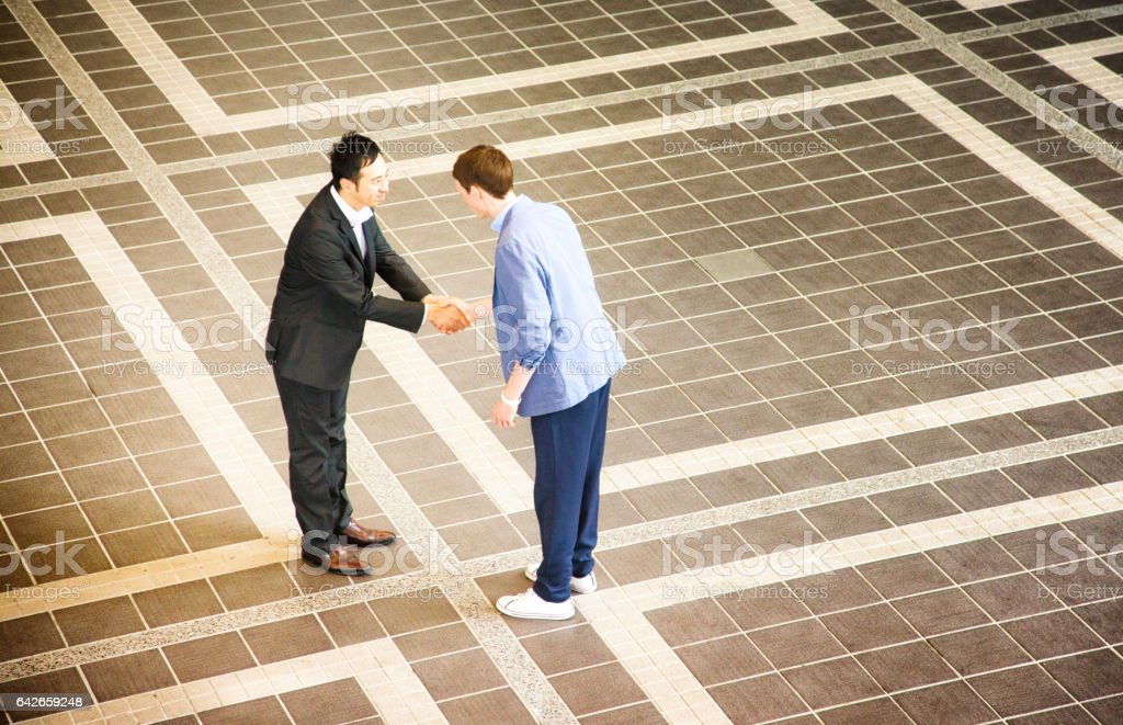 Two businessmen meeting in Japan and shaking hands stock photo