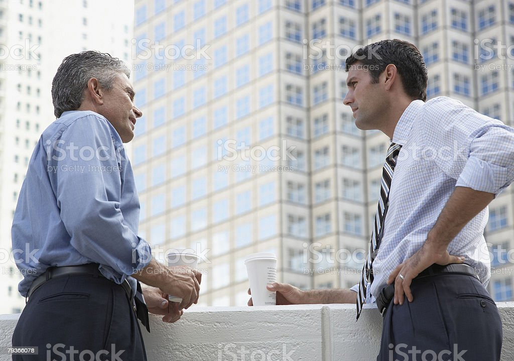 Two businessmen outdoors on a balcony with coffee cups royalty-free stock photo