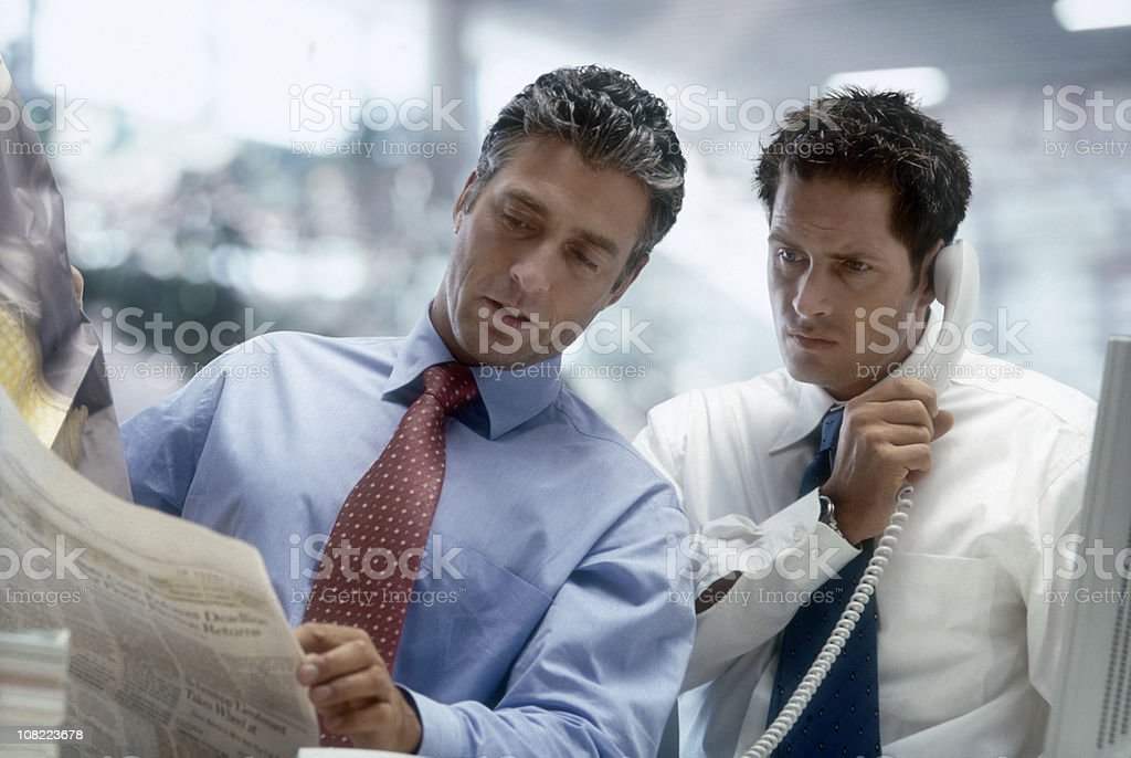 Two Businessmen Reading Newspaper in Office royalty-free stock photo