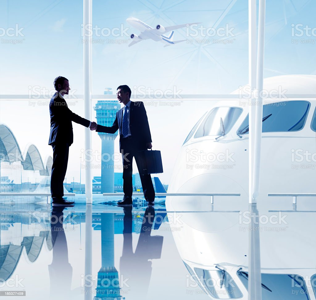 Two businessmen shaking hands at an airport royalty-free stock photo