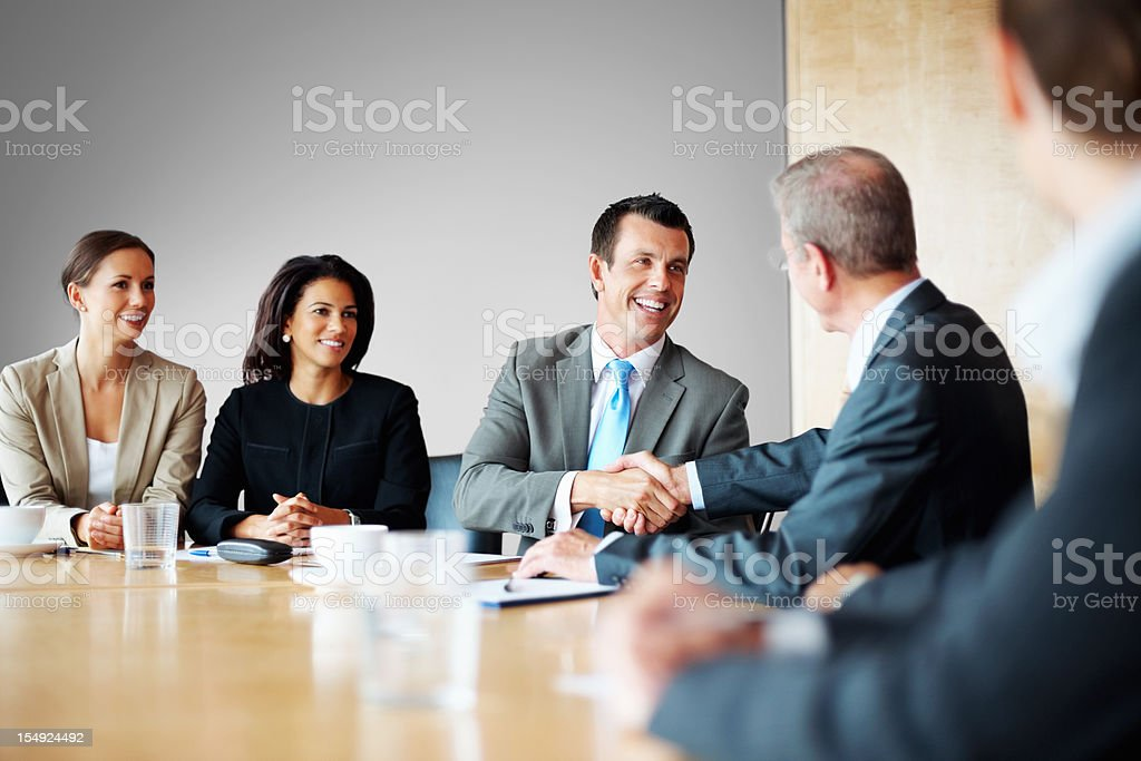 Two businessmen shaking hands in a conference room royalty-free stock photo