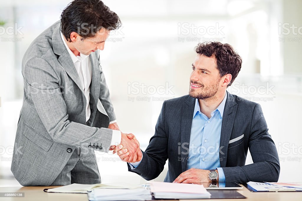 Two businessmen shaking hands in boardroom stock photo