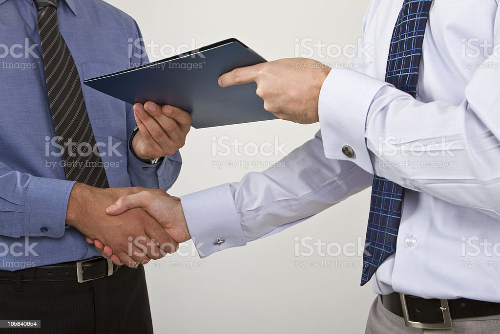 Two businessmen shaking hands on a deal stock photo