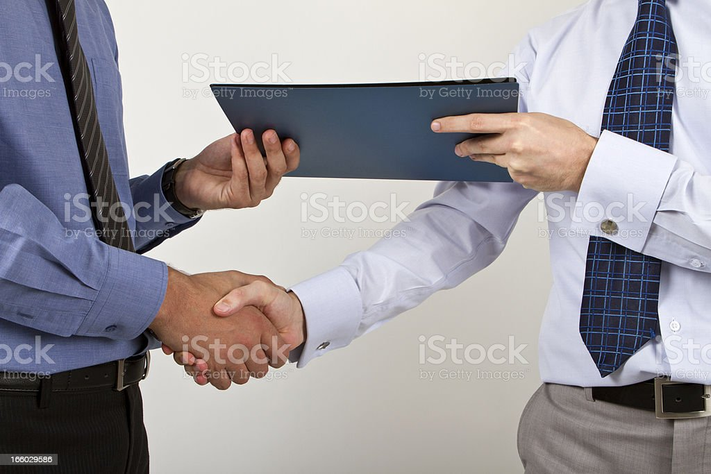 Two businessmen shaking hands with a document stock photo