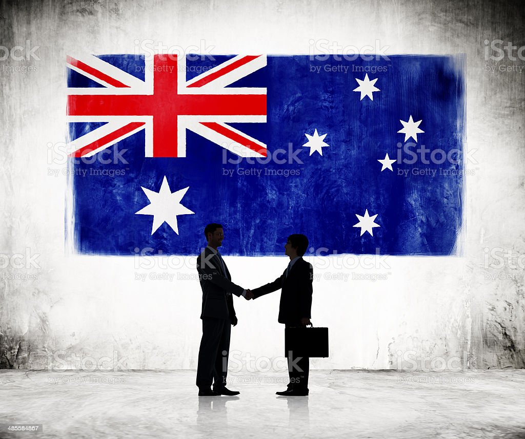 Two Businessmen Shaking Hands With Australian Flag As A Background stock photo